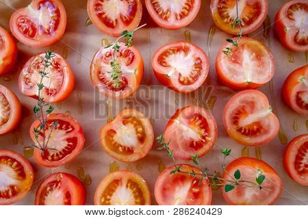 Preparing tomatoes for sun drying or roasting. Cut tomatoes, with fresh thyme and olive oil, on baking parchment. Top view horizontal format.