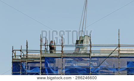 Gosford, New South Wales, Australia - November 30, 2018: Crane Operator In Control Of Equipment Deli