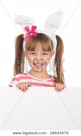 Easter concept image. Portrait of happy little girl with bunny ears and empty white board over white background.