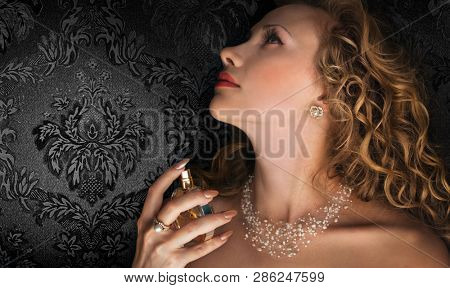 Beautiful young woman with perfume on dark background. Space for text.