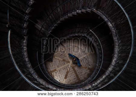Young Woman Standing In Center Of An Spiral Staircase, Top View