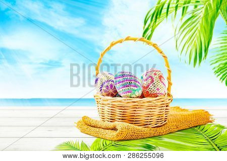 Colorful Easter Eggs On Wooden Basket With Fabric And Palm Leaf Mat On Wooden Table With Palm Branch