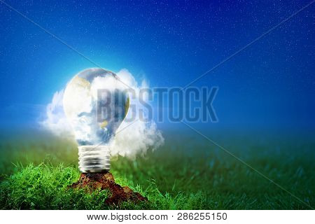 Earth Inside Light Bulb With Mist On The Soil In Meadow At Night With Star On The Sky Background. Ea