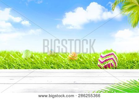 Colorful Easter Eggs Hidden On Grassland With Wooden Table And Palm Branches Over Blue Sky Backgroun
