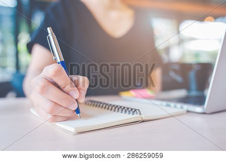 Business Woman's Hand Is Writing On A Notebook With A Pen.