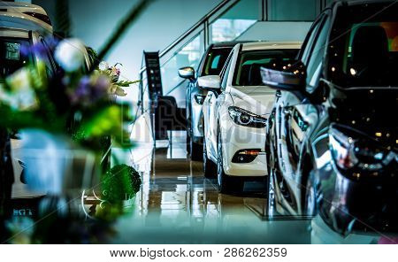 New Luxury Shiny Compact Car Parked In Modern Showroom. Car Dealership Office. Car Retail Shop. Elec
