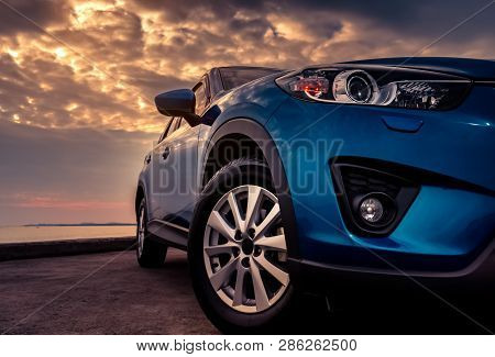 Blue Suv Car With Sport And Modern Design Parked On Concrete Road By The Sea At Sunset In The Evenin