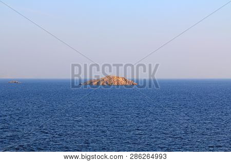 A textured background of some of the thousands of small uninhabited greek islands in the calm open w