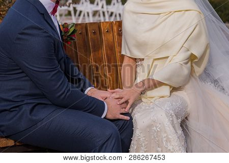 The Bride Is Sitting On A Bench With Her Fiance