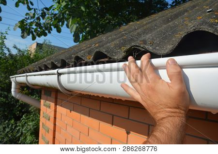 House Asbestos Roof With Plastic Roof Gutter Pipe Repair. Contractor Hand Repair House Roof Gutter.