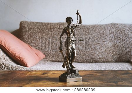 Lady Justice Or Justitia Statue On Table In Living Room - Landlord And Tenant Law Or Right Of Reside