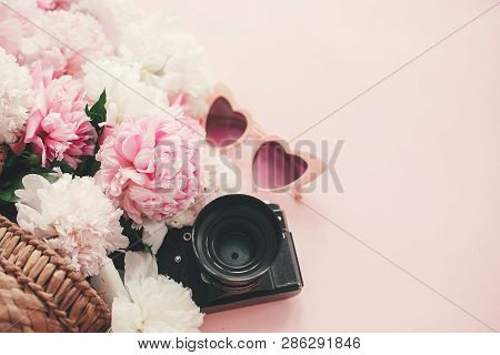 Stylish Photo Camera, Sunglasses, Straw  Bag With Pink And White Peonies On Pink Paper Flat Lay With