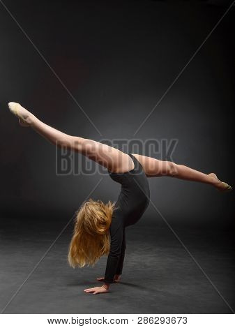 Young Beautiful White Caucasian Girl Gymnast With Long Hair Doing Gymnastic Exercise On Black Backgr
