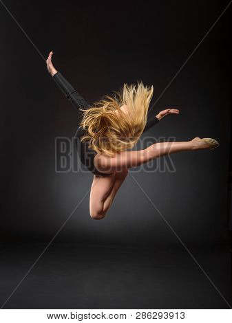 Young Beautiful White Caucasian Girl Gymnast With Long Hair Jumps On Black Background.