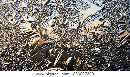 Close Up Of Small Ice Crystals On A Glass Window Pane With Gradient From Orange To Blue Morning Sky