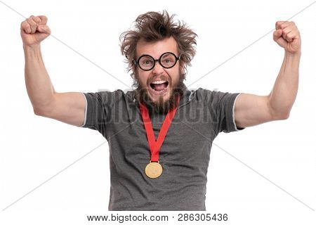 Happy winner. Crazy bearded Man with funny Haircut in eye Glasses celebrating his success. Cheerful Guy with gold Medal, screaming and keeping mouth open, isolated on white background.