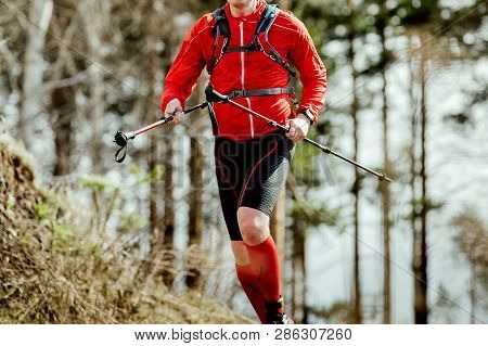 Athlete Skyrunner With Trekking Poles In Hands Running Uphill In Forest