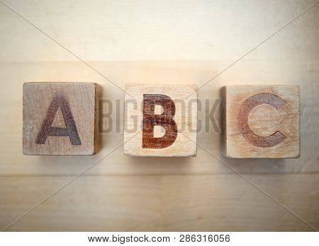 Wooden Alphabet Blocks Spelling Abc On Hardwood Floor. Educational Toys For Children In Preschool An