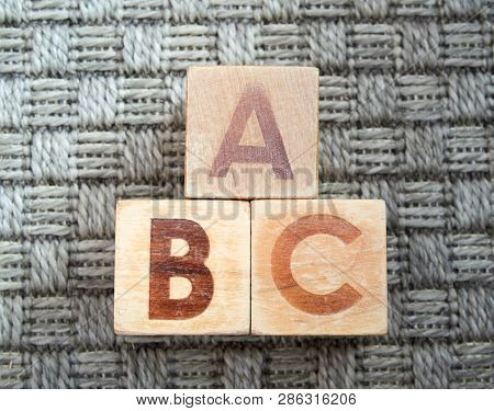 Wooden Alphabet Blocks Spelling Abc On Grey Carpet. Educational Toys For Children In Preschool And K