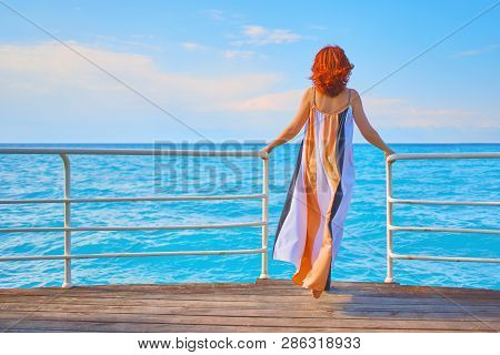 Behind Girl On Pier. Back View Of Red Head Girl On Pier.