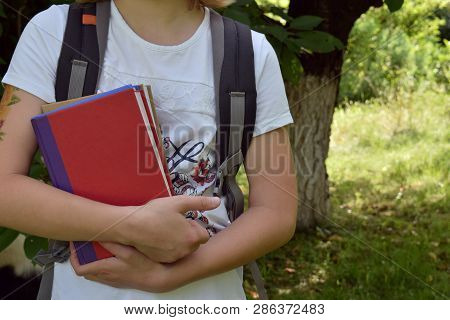 Back To School Concept. Teenager With A School Bag Holding Books In Hands