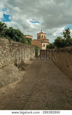 Alley In A Cloudy Day With Stone Walls Going Towards The Santa Maria La Mayor Church And Steeple At