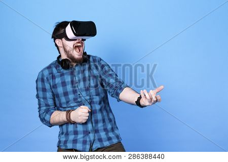 bearded man in glasses of virtual reality, emotionally playing shooters in VR on blue  background poster