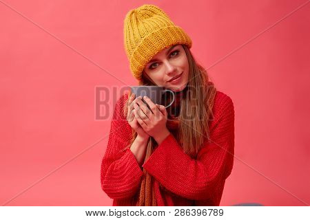 Beautiful Teenage Girl In Warm Cozy Sweater With Cup Of Hot Drink. Red Background. Studio