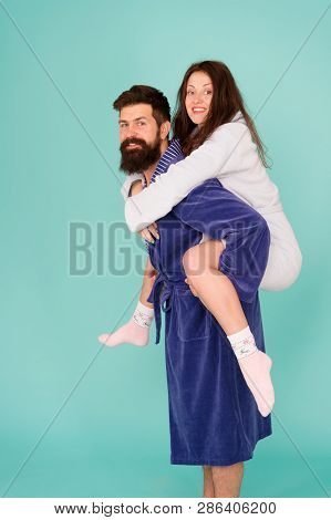 Handsome Young Man Piggybacking Beautiful Woman. Couple In Bathrobes Having Fun Turquoise Background