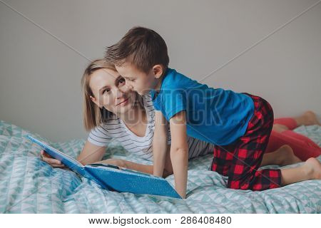 Family Of Two People Sitting On Bed In Bedroom Reading Book. Mother And Boy Son At Home Spending Tim