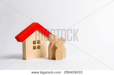 Figures Of The Family And House On A White Background. Real Estate, Your Own Home. Buying Or Selling