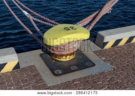 Ship Mooring Rope Moored On The Bollard. Moored Boat In The Port.  Season Of The Spring.