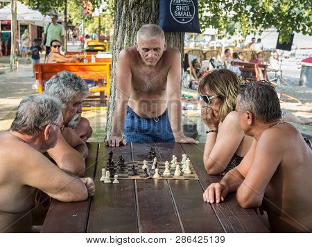 Novi Sad, Serbia - July 25, 2015: Old Men Playing Chess In Swisuit On A Table In A Park Of Novi Sad,