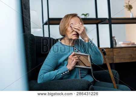 Grieving Senior Woman Sitting In Armchair, Covering Face With Hand And Crying While Holding Picture