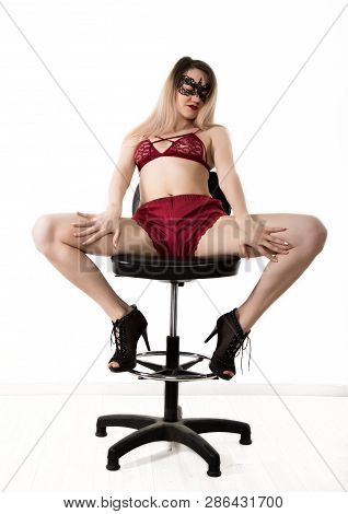 Sexy Elegant Woman In Red Lingerie And Lace Mask Is Posing While Sitting On A High Chair And Spreadi