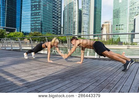 Beautiful Fitness Young Sporty Couple Doing Push Ups Together Outdoors