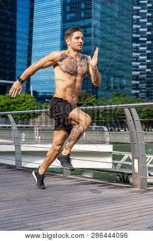 Athletic Young Man Sprinting Through The City On The Waterfront