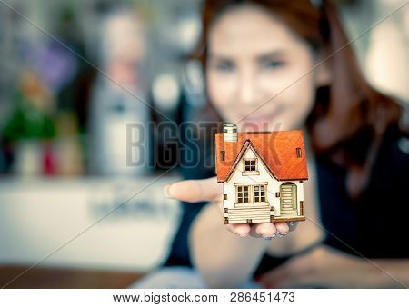 Hands Of Business Woman Holding House Key And House,real Estate And Property Concept.