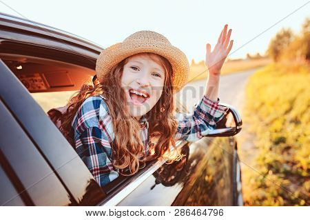 Happy Child Girl Looking Out The Car Window During Road Trip On Summer Vacations. Summertime, Explor