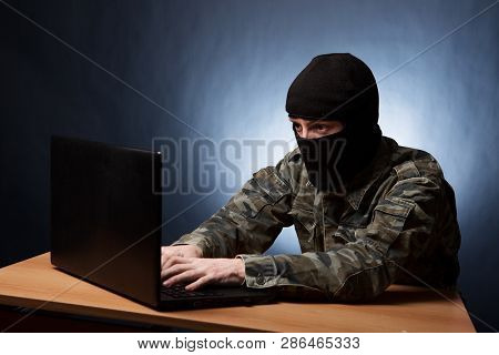 Terrorist Working On His Computer. Masked Cyber Terrorist Hacking Army Intelligence