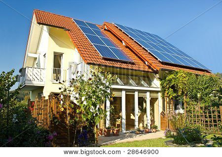 House with garden and solar panels on the roof