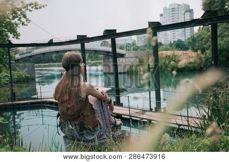 Young Hippie Woman Sitting Near A City Pond
