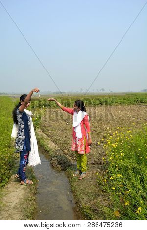 1843067c73 Close Up Of Two Young Girls Standing Outside In A Field On A Water Canal  Taking
