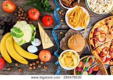 Fastfood And Healthy Food On Old Wooden Background. Concept Choosing Correct Nutrition Or Of Junk Ea