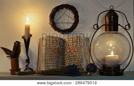 Open witch book with spells, old-fashioned lamp, candle and pentagram. Magic gothic ritual. Wicca, esoteric, divination and occult background with vintage objects poster