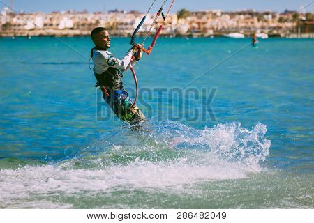 Egypt, Hurghada - 30 November, 2017:The kitesurfer gliding on the Red sea waves. The outdoor water sport activity. Popular tourist attraction. The Panorama Bungalows Aqua Park Hotel background.