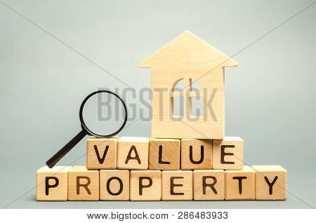 Wooden blocks with the word Value Property and the house with a magnifying glass. The study of the state of the house / housing. Home Inspection / valuation. Appraisal real estate poster