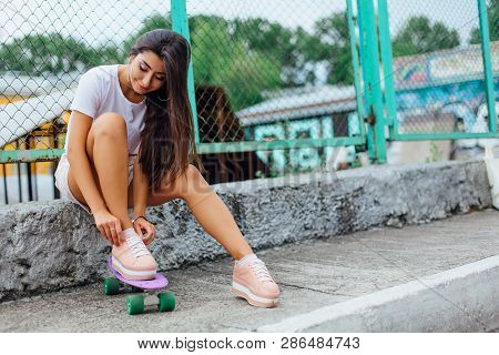 Summer Lifestyle Image Of Trendy Pretty Young Girl Sitting Next To The Skateboard Coart With Her Pla