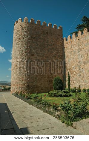 Back of the Cathedral merged with the city wall made of stone, in a sunny day at Avila. It has the longest and imposing wall completely encircling this well-kept gothic town in Spain. poster