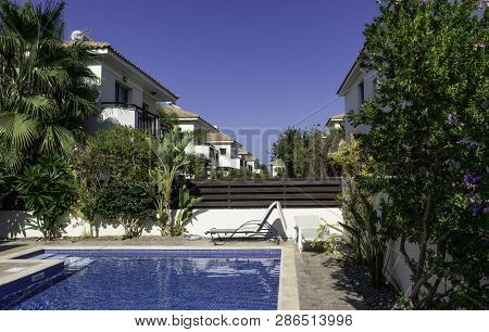 View From The Side Of The Pool With Clear Water On The Roofs Of The Neighboring Villas. The Pool Is